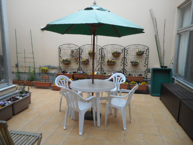 中庭に置かれた白いパラソル付きテーブルの写真